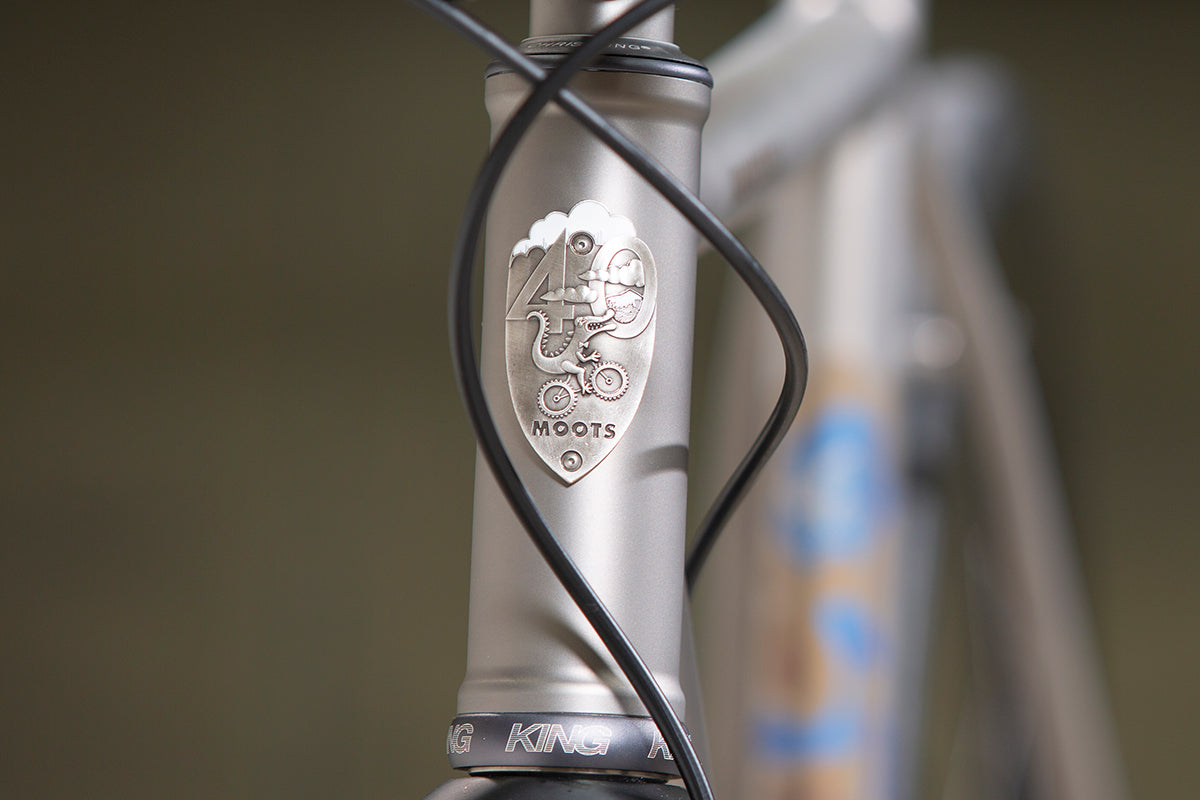 Close up showing the 40th anniversary Moots head badge with Mr Moots riding a bike