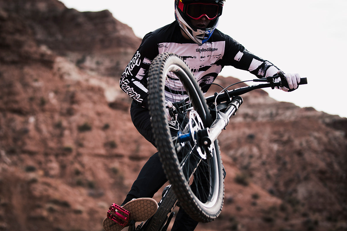Action shot of a mountain biker wearing the Troy Lee Designs Sprint kit whilst doing air off a jump