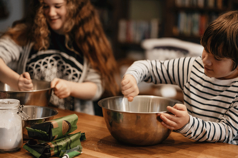 brother and sister at kitchen counter stirring metal bowls