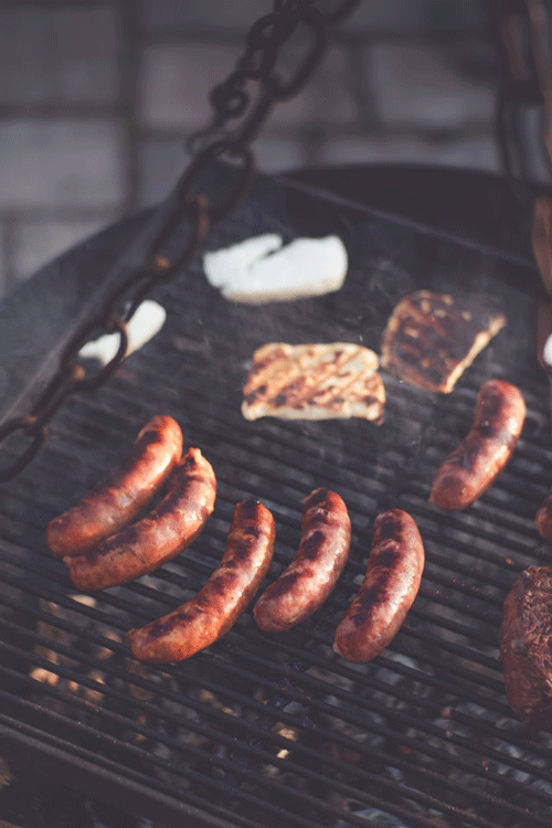 close up of hot dogs on a grill