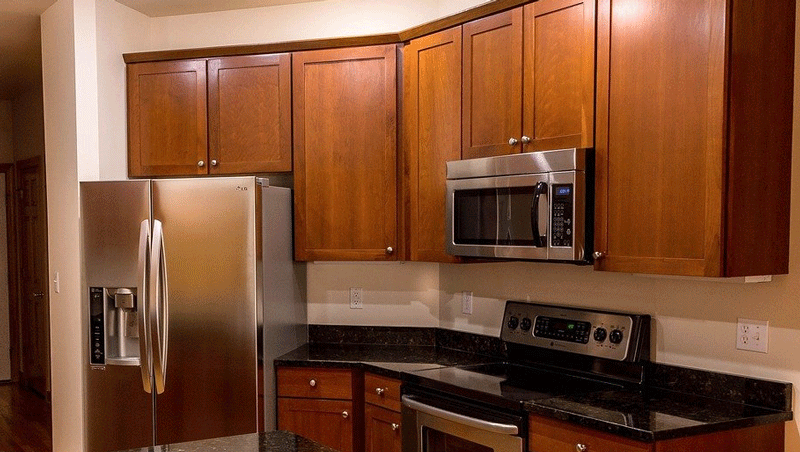 cropped shot of countertops and microwave suspended from cabinetry