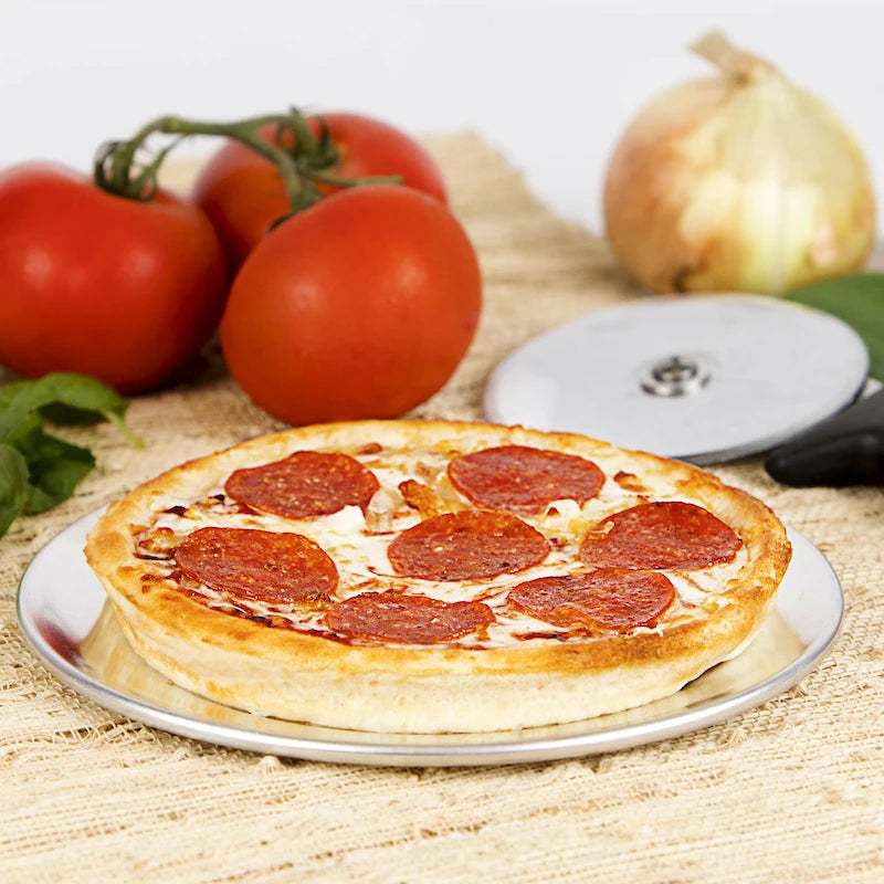 A personal pepperoni pizza with tomatoes and onion in the background.