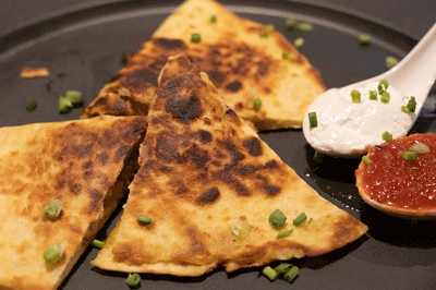pieces of cut-up quesadilla on black plate
