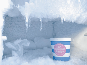 tub of ice cream inside heavily iced freezer