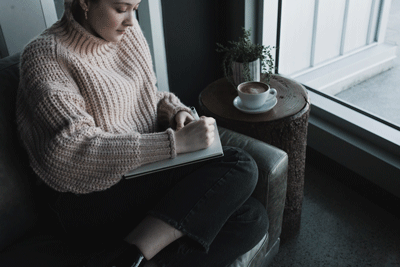 woman journaling on sofa beside cup of coffee