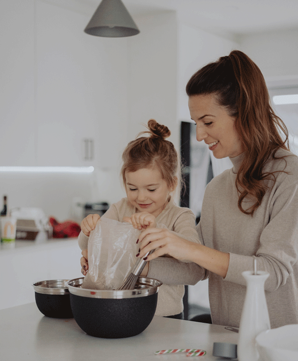 young daughter helping mother add bag of food to bowl