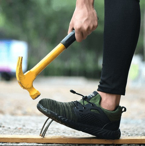Hitting Defender Pro's Steel Toe with a yellow hammer.