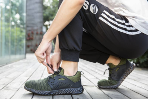 Person tightens emerald Defender Pro Shoes on feet