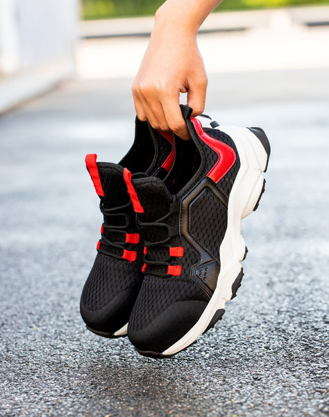 Someone holding a pair of red and white Guardian Shoes.