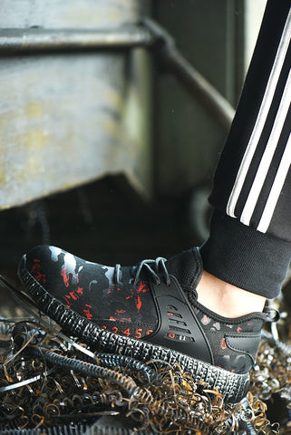 Person standing outside wearing red camouflaged Ghost Shoes on metal fragments