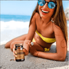 girl on the beach holding a bottle of dr.viton bronzan sunless tanning capsles