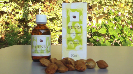 hunza apricot kernel oil and packaging with kernels in front of them