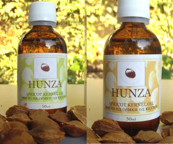 two bottles of hunza apricot oil, one sweet one bitter, with apricot kernels in the front