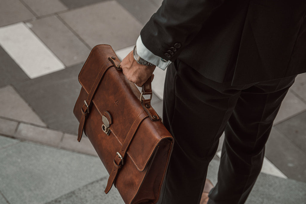 man carrying brown messenger briefcase