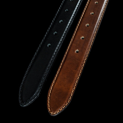 Black and brown Von Baer belts isolated against a black background