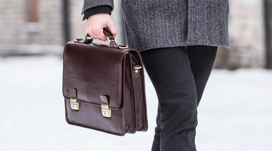 brown leather briefcase held by man outside