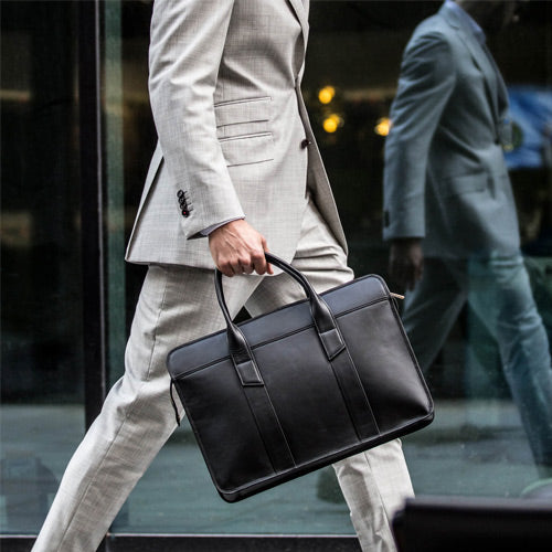 man walking with black leather laptop bag