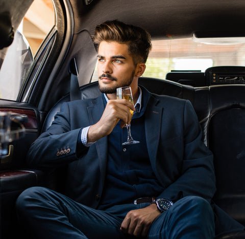 Young businessman sitting in limousine with wine in hand