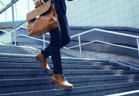 Man dressed in suit with leather shoe and briefcase walking down the stairs