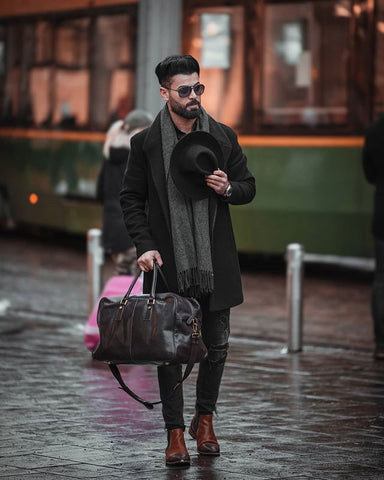 Stylish man with a carry-on bag just returning from a journey