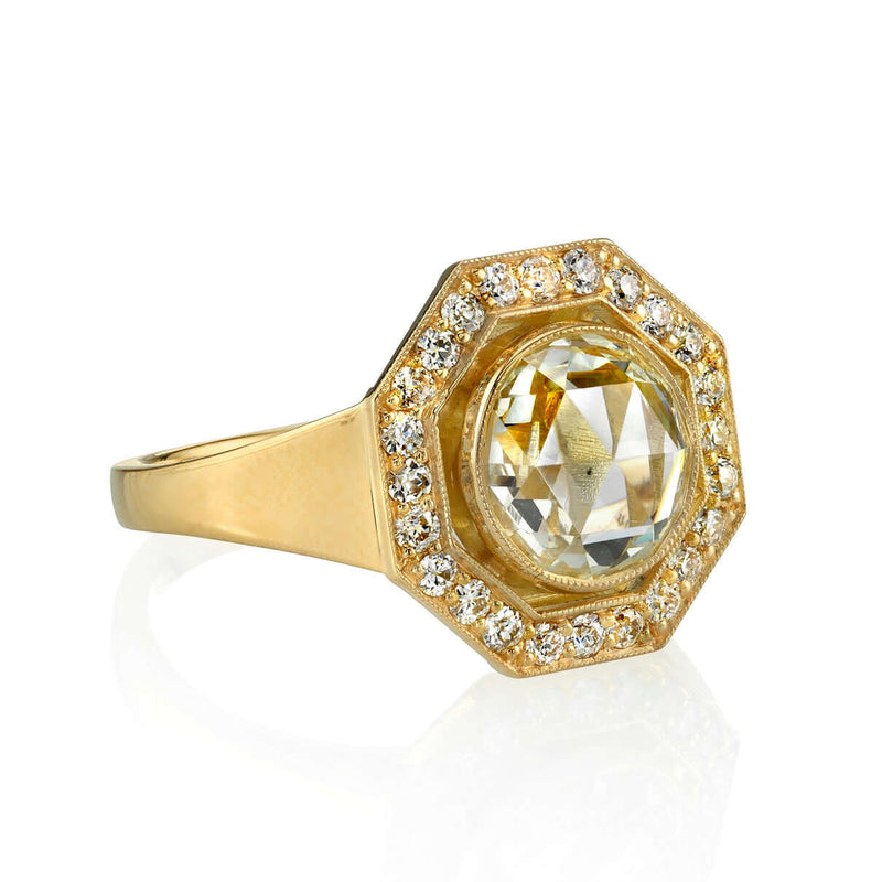 SIDE VIEW OF AN 18K YELLOW GOLD DIAMOND RING SHOWCASING A HALO OF ACCENT DIAMONDS | SINGLE STONE