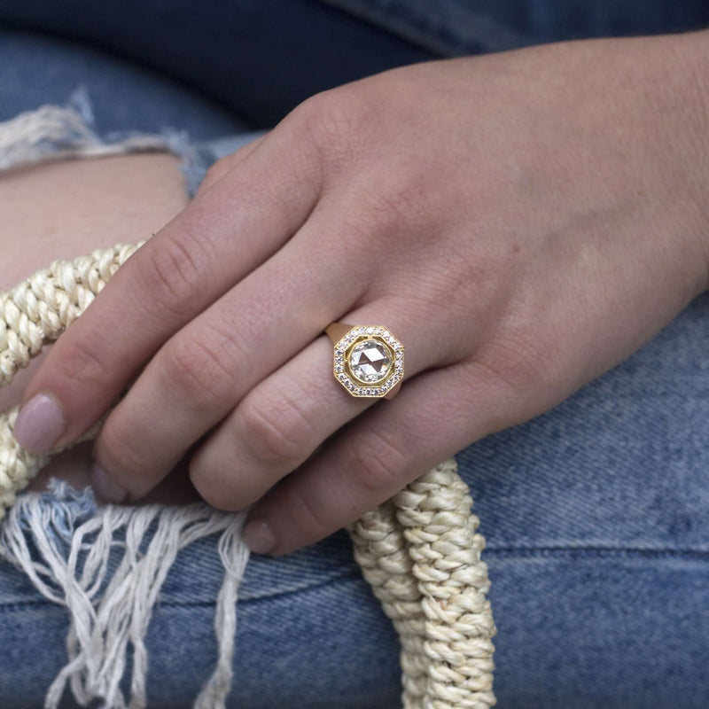 WOMAN'S HAND DRAPED OVER KNEE WEARING 18K YELLOW GOLD DIAMOND RING | SINGLE STONE
