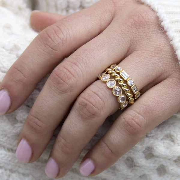WOMAN'S HAND WITH STACKED RINGS INCLUDING TWISTED 18K YELLOW GOLD BAND | SINGLE STONE