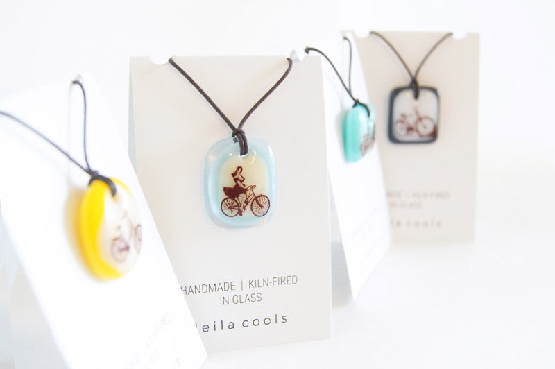 Handmade fused glass pendant necklaces on retail display cards for wholesale purchase.