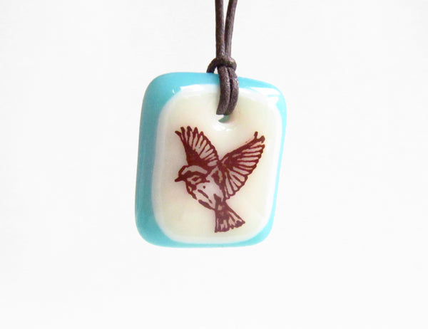 Flying bird necklace in blue and cream glass.