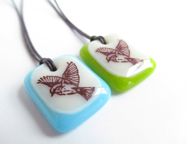Bird in Flight pendants on cord necklaces.