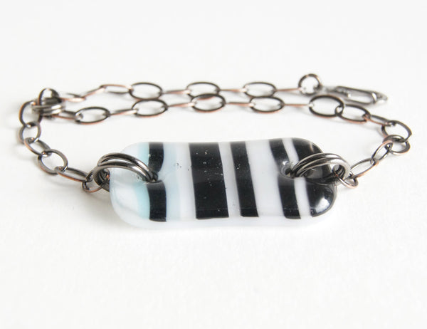 Black and white striped glass bracelet on adjustable bronze chain.
