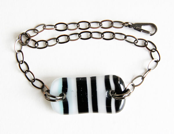 Fused glass bracelet with black stripes on white handmade by Leila Cools.