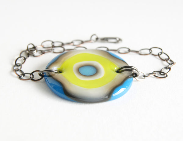 A fun bold glass and chain bracelet with a blue and green bullseye design.