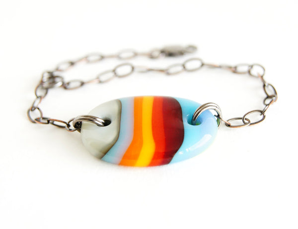 Handmade adjustable bracelet with multicolor striped glass oval bead.
