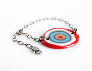 Adjustable chain bracelet with red and blue glass bullseye design