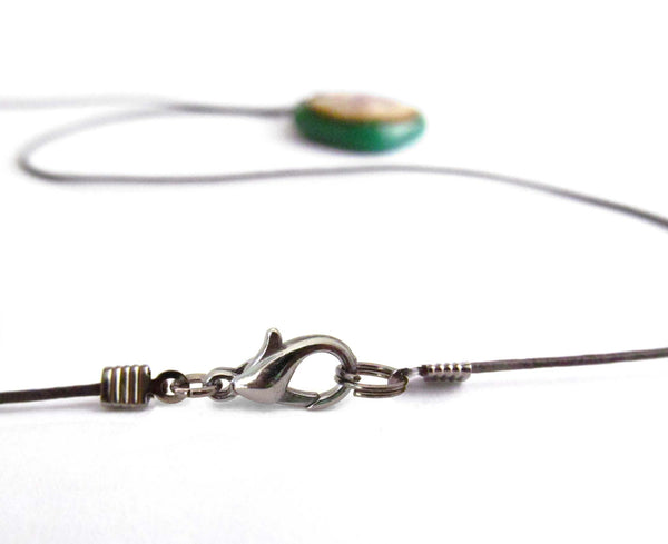 This pendant is on a brown cord necklace with a claw clasp.