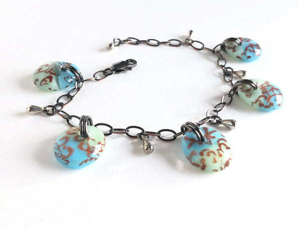 One of a kind adjustable fused glass bracelet with antiqued bronze chain and stainless steel tear drop beads.