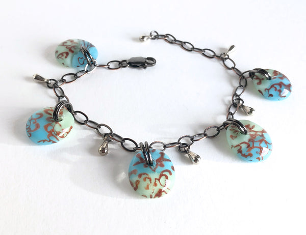 Charm bracelet with sepia tone filigree design on blue and green glass.