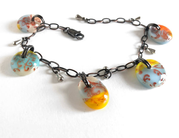 A fused glass bracelet with vintage style glass drops, filigree design and adjustable bronze chain.