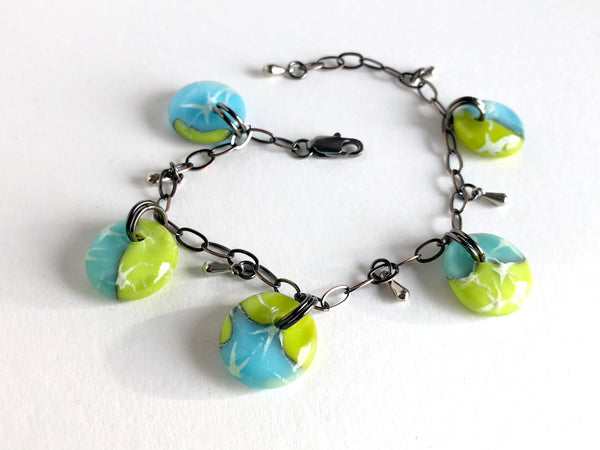 Glass drop bracelet in aqua blue and light olive green / chartreuse with painted silver stars