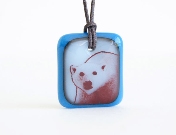 Polar bear necklace in royal blue and milk white glass.
