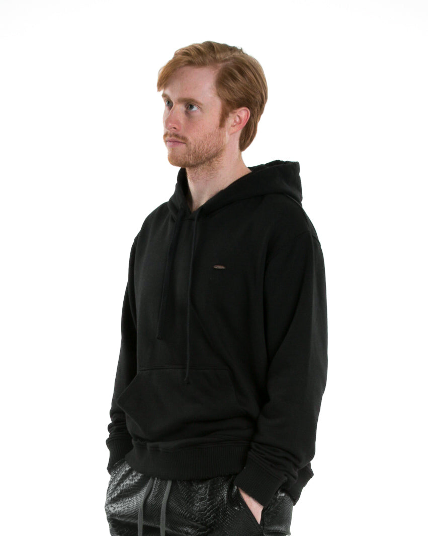 Side of male model wearing Weighted Hoodie in Black
