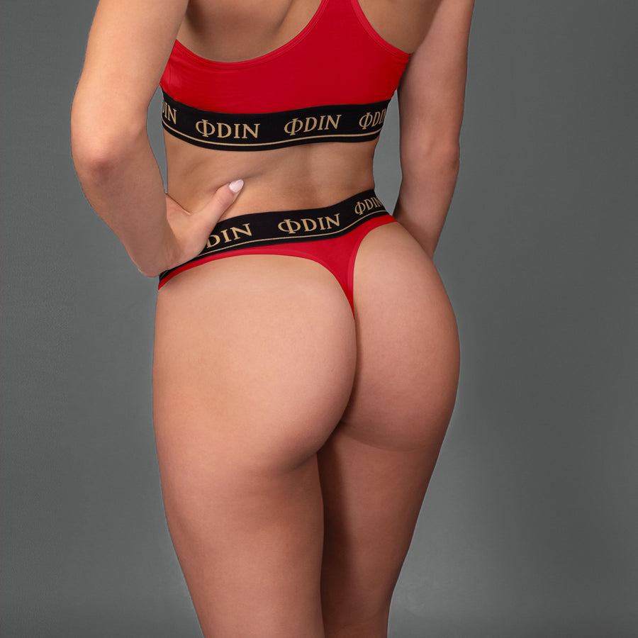 suspended red  gym thong for workout. The black elastic band reads ODIN. This is the perfect gym gear for women.