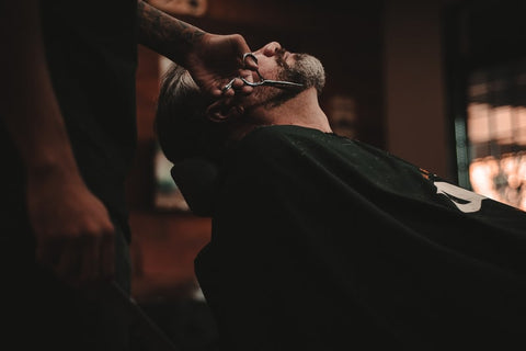 A man sitting back in a barber's chair, getting his beard trimmed