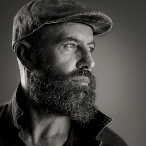A black and white shot of a man with a thick beard gazing to the right, wearing a cap.