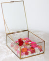 orange infinity rose arrangement in a brass box