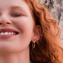 Close up of model wearing petite grand gold atlantis earrings
