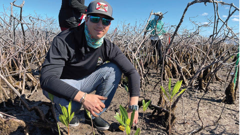 Kyle Rossin planting mangroves on Grand Bahama Island during hydrologic surveying.
