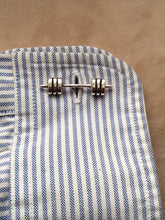 Barbell cufflinks shown on shirt