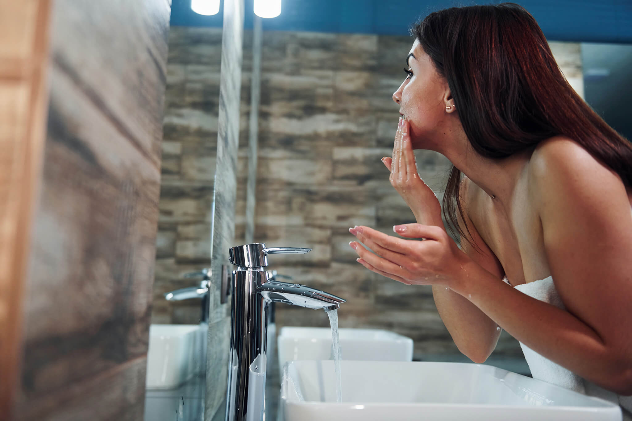 A young woman washing her face using SLMD Skincare Salicylic Acid Cleanser